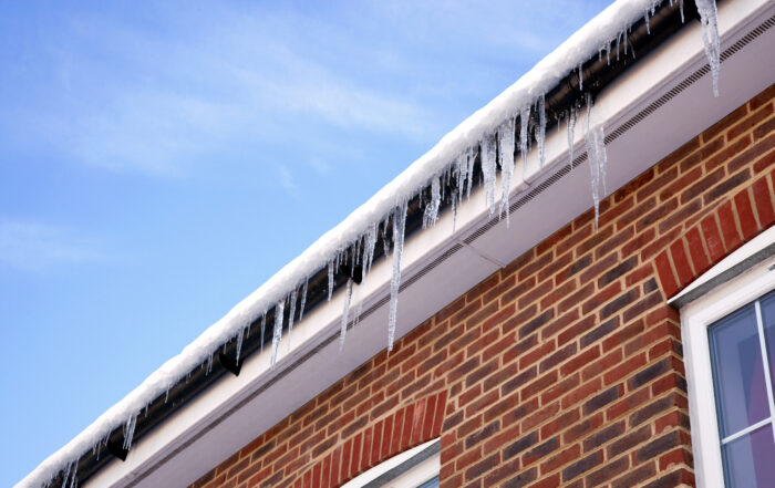 Winter image of icicles hanging from the gutter on the snow covered roof of a modern house.
